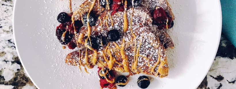 french toast with peanut butter and berries on white plate and marble counter